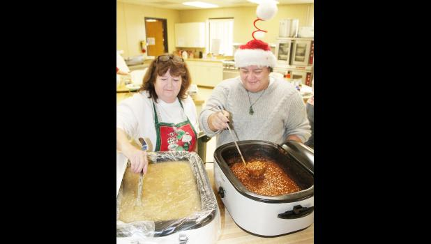 Teresa Scheidegger (left) stirred the gravy for the mashed potatoes while Kiri Mock (right) made sure the beans were ready to serve at Wednesday's Community Christmas Dinner at the EUM Family Life Center. Dinner organizer Tammy Elliott said about 200 meals were served at the Family Life Center and 44 meals were delivered for this year's dinner, a community event since 1985. (Photo by Brian Sanders)