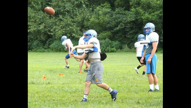 Holton quarterback Justin Rieschick (shown above, middle) lobs a pass to a running back as the Wildcats worked on their routes during practice on Tuesday.