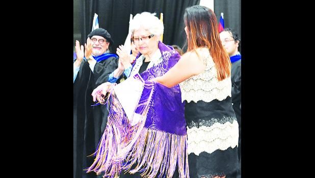 Helen Sumner of Hoyt (center) is shown receiving a Native American shawl from Brittany Hall (right), Haskell Foundation administrator, after Sumner was named the Outstanding Alumnus of the Year.