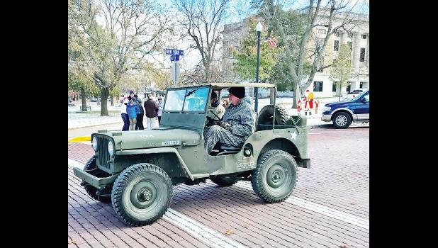 Walt Wells drove a jeep around Holton's Town Square (with David Roller as a passenger) in honor of his father, a military veteran, during Friday's Veterans Day Parade. (Photo by David Powls)
