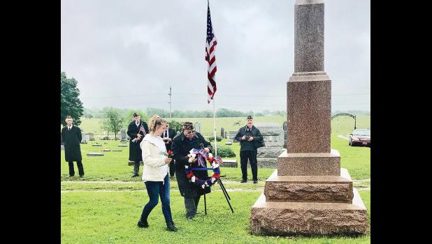 Lucy Ryff (third from left) and area veteran Franklin Peuker (second from right) carried a wreath and flowers to the Civil War memorial at Monday's Memorial Day ceremony in Holton Cemetery, conducted jointly by Holton's American Legion and VFW posts. Looking on in the background were local veterans (from left to right) Bob Schiffbauer, Ryff's grandfather; Les Crawshaw; John Chiles (partially hidden); and Gregg Moser. (Photo by David Powls)