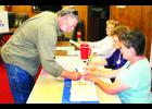 Mark McKinsey of Holton (left) signed in to vote during Tuesday's general election with some help from election volunteers Gayle Dunn (right), Cletamae Brown (second from right) and Carol Baum at the Veterans Club. Tuesday's election was the first to be held at the Vets Club, as opposed to the former Jackson County Fair Building, a polling place for Holton voters in previous elections. Signs were placed outside the old fair building to remind people of the new polling place.