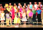 "Third-grade students at Central Elementary School performed ""The Granny Awards"" at their spring concert last week, which featured characters from a variety of fairy tales. In the photo above, Snow White (center), played by Mariah Woltje, sang a song under the direction of Sheri Bartel (left), music instructor."