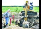 Holton Water and Wastewater Superintendent Dennis Ashcraft (left) watched as Monte McDaniel of Tonganoxie's Kansas Heavy Construction dug out a trench at the Holton Industrial Park so that Ashcraft and others from his department could remove an old waterline in preparation for KHC's work on rebuilding the roads in the industrial park. Justin Wensel, project manager for KHC, said it is likely that road work in the park will begin sometime next week.