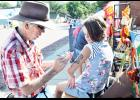 A variety of activities were held during Mayetta Pioneer Day on Saturday in downtown Mayetta. Here, Charles Moore (at left) offered face and body painting throughout the event. Moore is shown with Marisa Meyer of Holton. (Photo by Ali Holcomb)