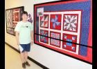 Royal Valley Middle School educational technology specialist Brenda Hainey is shown here with three quilts that she and sixth-grade students, along with some volunteer help, created for the Quilts of Valor program. The school is seeking names of local war veterans for a drawing, and the three quilts will be presented to the drawing's winners at an upcoming Veterans Day assembly at RVMS. (Photo by Brian Sanders)