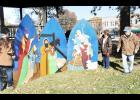 Local artists Mary (far left) and Gary Shupe (far right), along with Sandy Studebaker (second from right) painted these three panels depicting the nativity scene, recently installed on the south side of the Jackson County Courtyard. Several other painted Christmas motifs can also be seen throughout the courtyard. (Photo by Ali Holcomb)