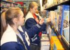 "Holton High School students Tabor Barta (left) and Lauryn Moore placed stickers on cereal malt beverage products at Walmart on Friday morning to remind people not to buy those products for minors as part of the Jackson County Youth Coalition's annual ""Sticker Shock"" campaign. Deb Harshaw, who oversees the campaign, said nine local businesses agreed to participate in the campaign this year. (Photo by Brian Sanders)"