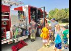 Hoyt Rural Fire District representatives Nathan Troxel, Monica Tinoco and Randy Smith, shown above left to right, helped local kids climb into one of their firetrucks at last Thursday morning's Sheriff's Day Camp. The camp activities attracted a record number of kids.