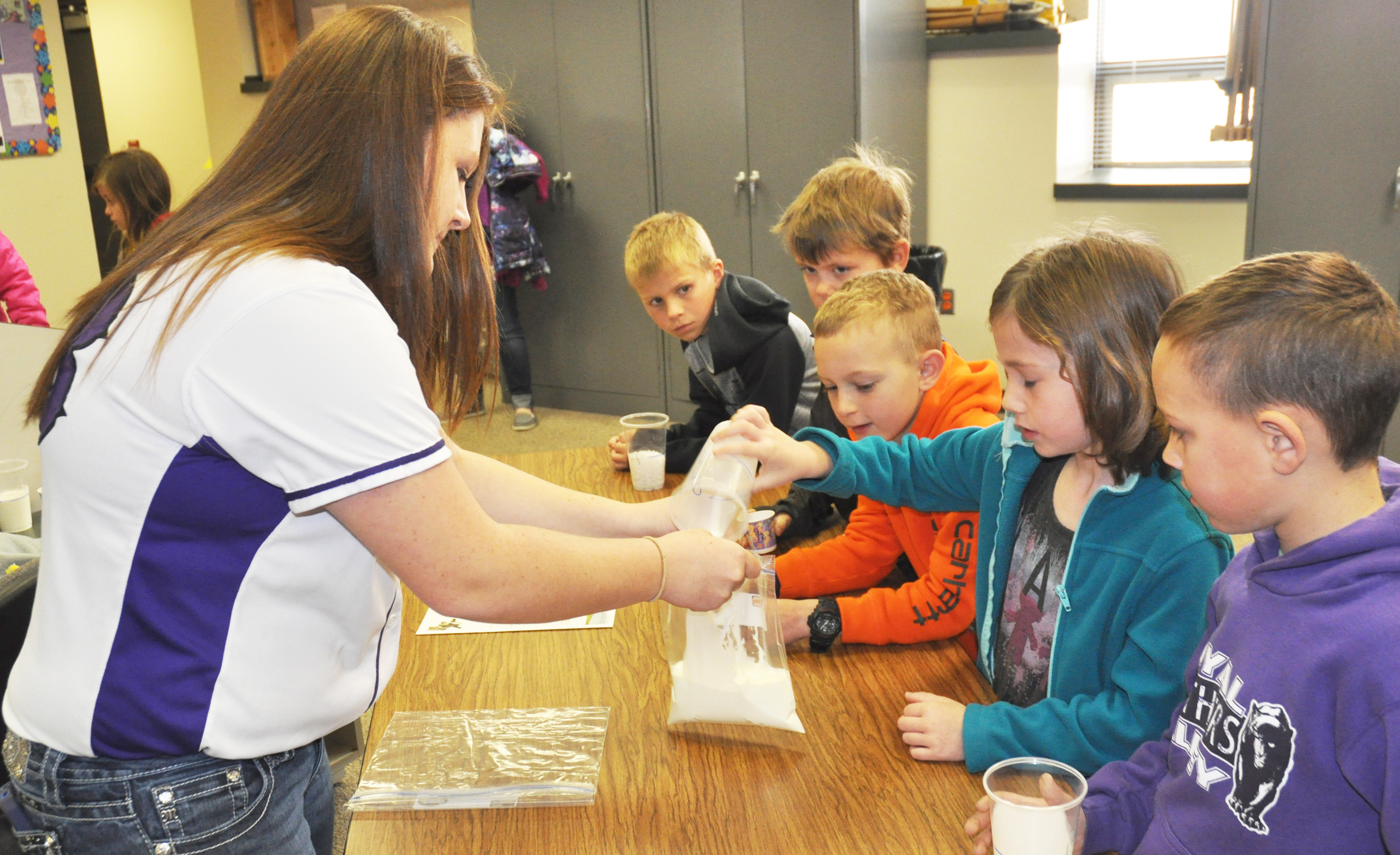 Royal Valley High School FFA member Eryn Daughtery (left) taught a group of second-grade students how to make ice cream by combining a few ingredients as part of the club's annual Elementary Agriculture Day last week. Elementary students pictured include (from front to back) Carter Russell, Isabella Wheeler, Wyatt Shields, John Young and Nolan Bausch. (Photo by Ali Holcomb)
