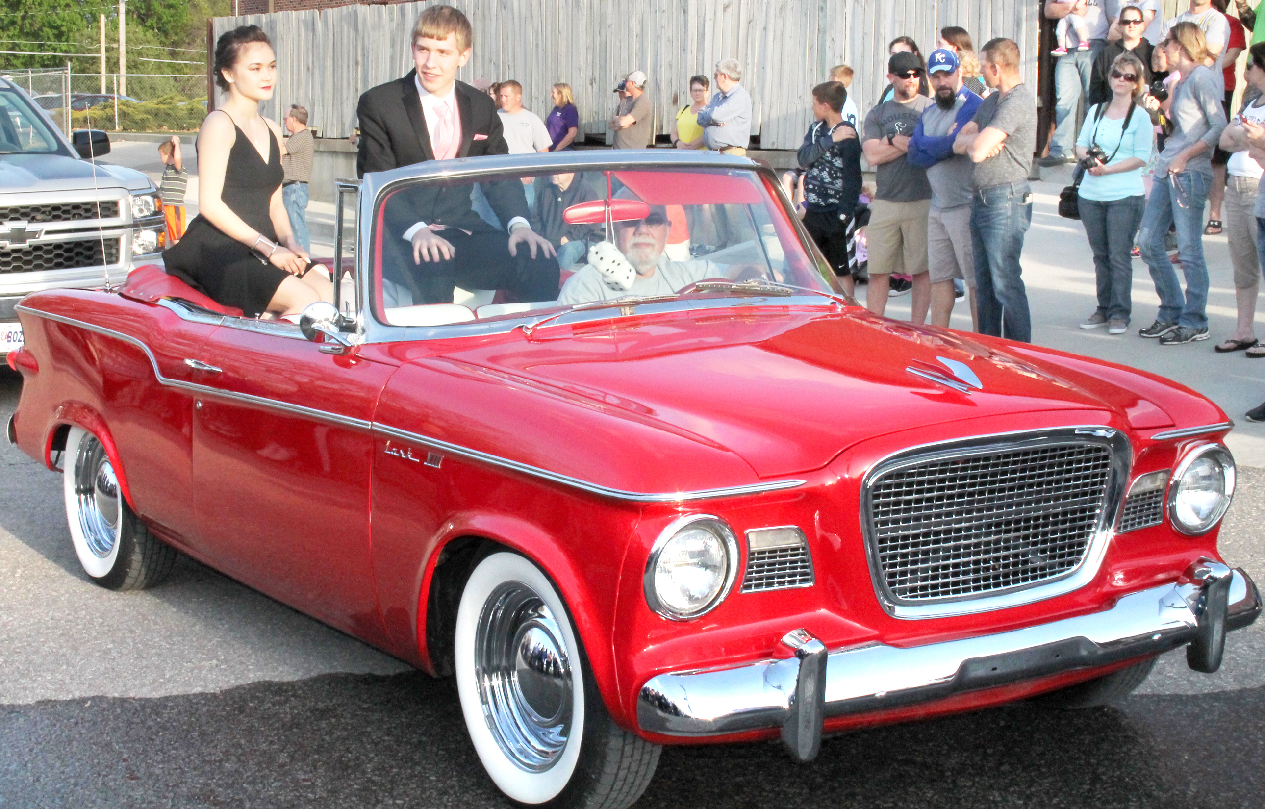 Holton High School seniors Abigail Heitzman (left) and Joel Cawby (center) rode to Saturday's HHS prom in the back of a Lark VIII convertible driven by Scott Bartlett while a crowd of family members and friends looked on. (Photo by Brian Sanders)