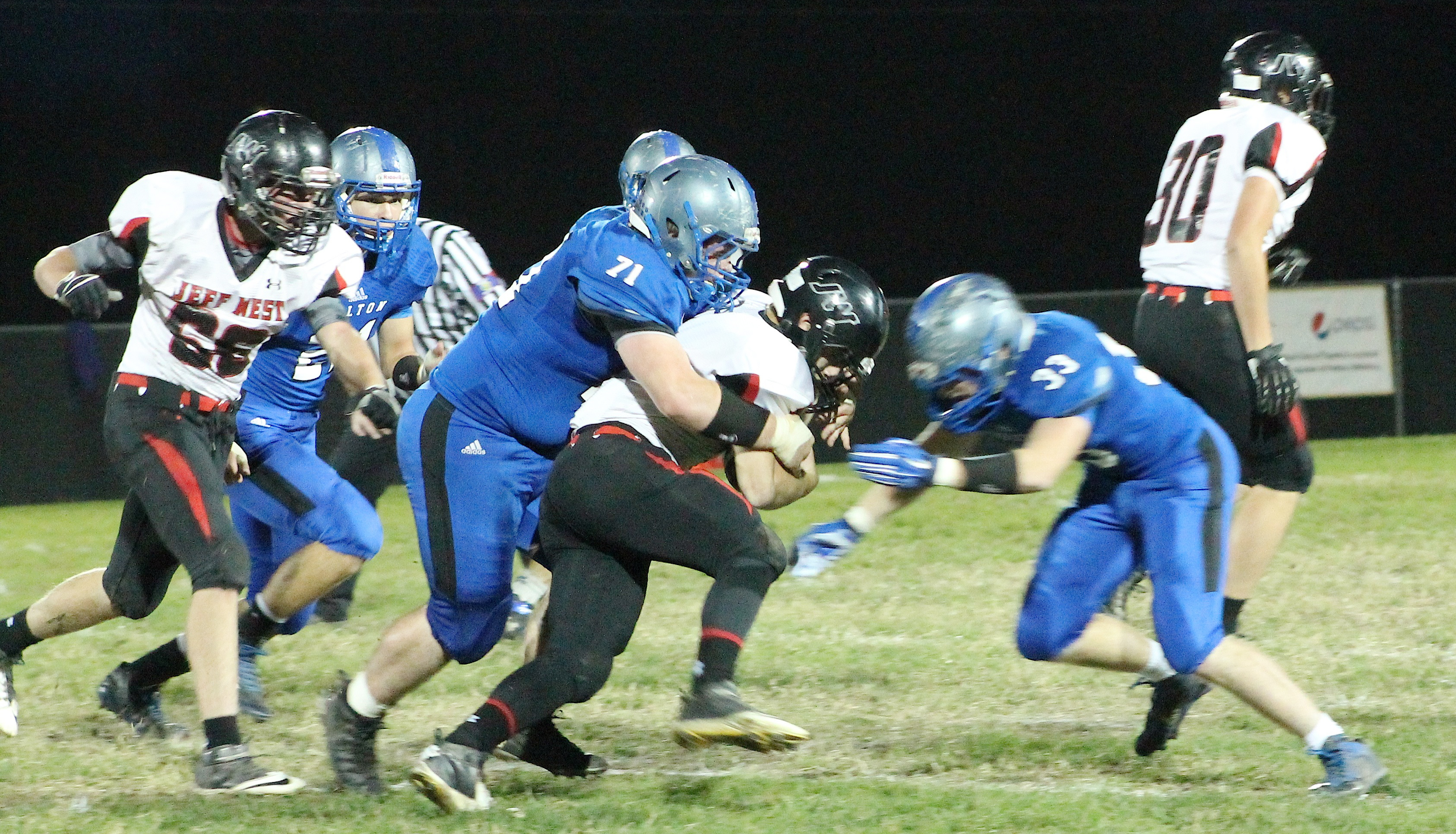 Lineman Cooper Allen (left) wraps up a Tiger running back while teammate Austin Frakes (right) closes in to assist on the tackle.