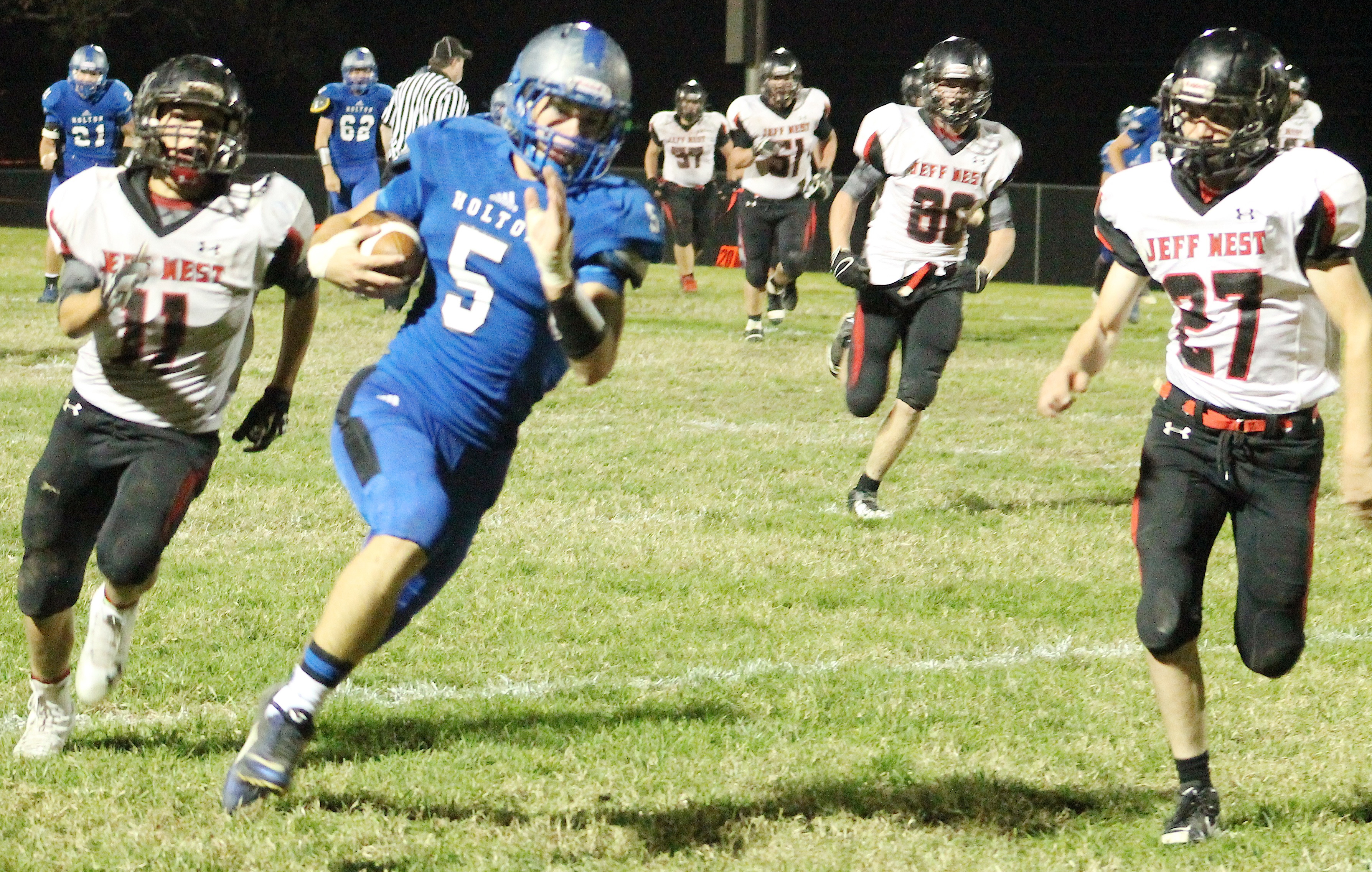 Wildcat Kaden Brandt (middle) turns upfield after hauling in a catch that set up one of Holton's three first half touchdowns.