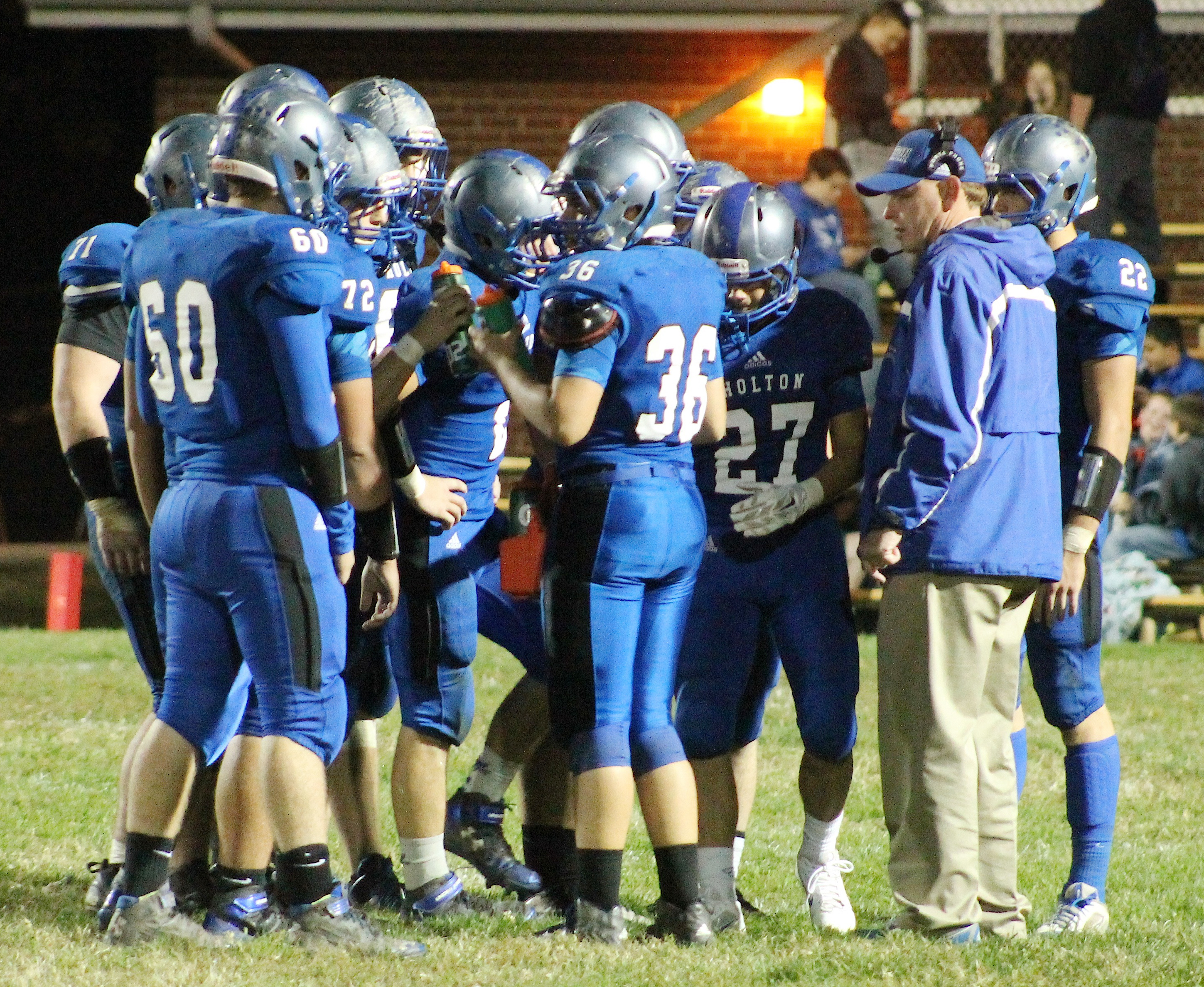The Wildcats huddle up and listen to coach Brooks Barta (right) during a timeout late in Friday's district football game.