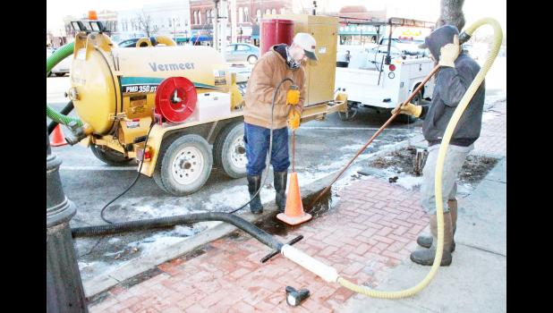 Cliff Givens (left) and P.J. Oldehoeft of Holton's water and sewer department spent Monday morning, Feb. 22 cleaning out a riser that goes down to a water service line valve on the south side of Holton's Town Square that was involved in a water line break over the weekend. City water employees and area plumbers noted a significant number of water line breaks due to recent cold weather, it was reported. (Photo by Brian Sanders)