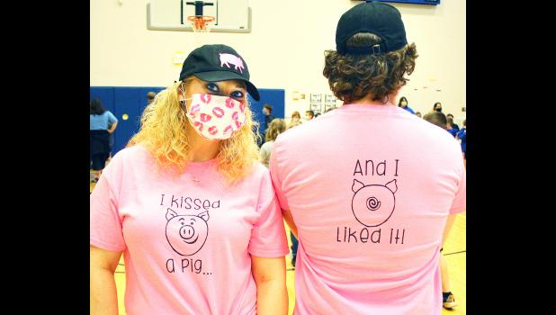 HES social worker Danyel Rockwell (left) and Assistant Principal Taylor Dunham showed off the commemorative T-shirts they wore while smooching the pig. (Photo by Brian Sanders)