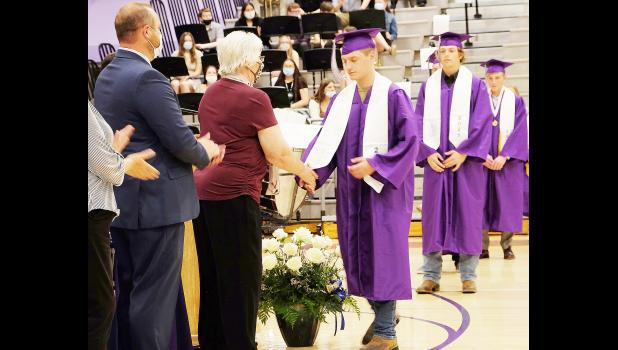 Royal Valley High School seniors Bryar Barnett (third from right), Kenneth Bell (second from right), Luke Boyden (partially hidden) and Caleb Boyer (at right) lined up to receive their diplomas at Saturday's commencement, which marked the 50th class of RVHS seniors to graduate from the district. (Photo by Ali Holcomb)