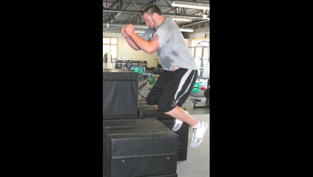 Forrestal Hickman (shown above) explodes upwards during a plyometric drill as part of a workout with Russ Riederer in the HHS weight room recently. The former Wildcat will be reporting to training camp with the San Diego Chargers at the end of the month.