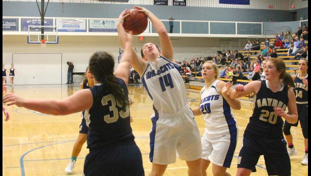 HHS guard Courtney Boswell (shown above, second from left) comes down with a rebound in the second half of Monday's home game against Hayden. Boswell helped Holton keep things close, but the visitors managed to pull out a 62-51 victory.