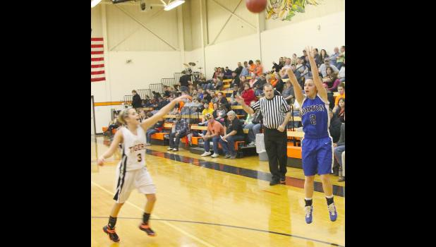 Wildcat Ashlyn Weilert (shown above, right) launches a three in the second half of last Friday's game against Atchison County. Weilert and the rest of the HHS team had a strong offensive showing on the way to a 63-50 victory.