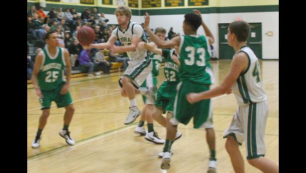 Cobra Korby Strube (shown above, middle) slices through the lane for a basket in Friday's home game against the Raiders. A lot of things went right for JHHS on offense as the team picked up a 50-27 victory in its first game.