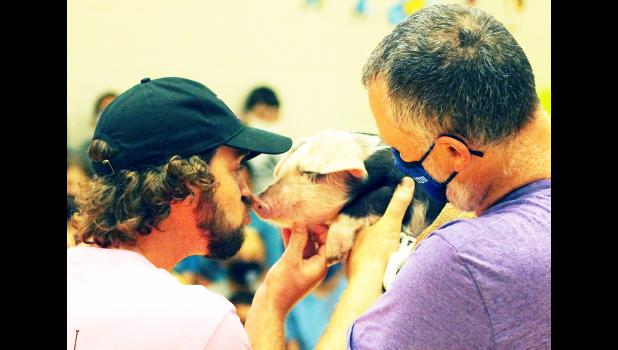 Holton Elementary School Assistant Principal Taylor Dunham, shown at left in the photo above, puckered up to kiss a pig held by Holton High School ag teacher Jason Larison (right) during a Monday morning celebration of a non-perishable food drive conducted by HES students that saw more than 1,100 food items collected for the JCMA Emergency Food Pantry. (Photo by Brian Sanders)