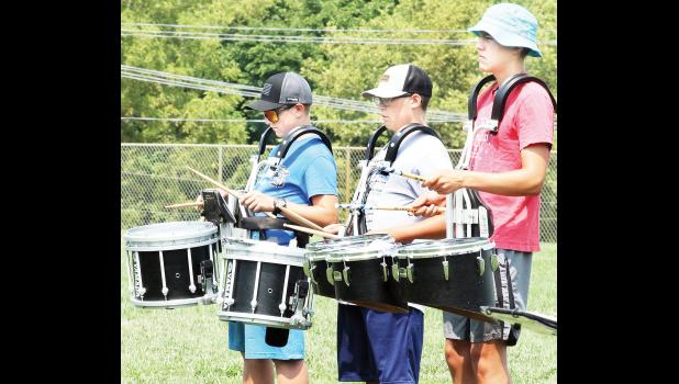Holton High School percussionists (from left to right) Tristan Simpson-Worley, Logan Heineken and Parker Crouch provided the backbeat for a HHS band exhibition performance last Friday at the HHS football stadium to note the end of the school's annual band camp. Band director James Malsom invited the public to see what the band has been working on for the upcoming school year. (Photo by Brian Sanders)