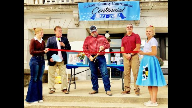 Jackson County Commissioner Ed Kathrens (center) prepared to cut the ceremonial ribbon on the Jackson County Courthouse's centennial celebration during Fall Fest activities while fellow commissioners Dan Brenner (second from left) and Keith Kelly (second from right) looked on while Annie Allen (left) and Amariah Allen held the ribbon. (Photo by David Powls)