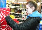 """Holton High School senior Olivia Yingst was among those applying stickers to cases of beer at Holton's Southside Liquor as part of the """"Sticker Shock"""" campaign, conducted over the school's holiday break by the Jackson County Communities That Care Coalition and the Jackson County Youth Coalition. The campaign's intent was to warn adults of the consequences of purchasing alcoholic beverages for minors. (Photo by Brian Sanders)"""