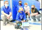 Dustin McBride, Holton Middle School technology teacher, is shown at left with a group of seventh-grade students as they work to code a robot to travel through the school. Coding, robotics and 3D printing are some of the options available to HMS students in tech courses offered by McBride. Seventh-graders shown with McBride include Kolbie Noel (front) and (back, from left) Jacob Warner, Andrew Keithley and Kylie Carlsen. (Photo by Ali Holcomb)