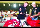 """Gunnery Sgt. Max Coons (left) of the U.S. Marine Corps and Jack Pittaway of the Holton VFW Riders stuffed red bags full of toys and other """"stocking stuffers"""" at the Holton National Guard Armory on Tuesday morning in preparation for distribution through the Toys for Tots program. This is the first year that the program, involving the collection and distribution of new toys to children in need during the Christmas season, has been done in Holton, Pittaway said, but the first time has been a huge success."""